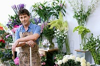 Male florist in apron standing in flower shop, leaning on broom beside display, smiling, portrait