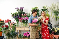 Male florist serving woman beside display in flower shop, holding bunch of flowers, woman choosing