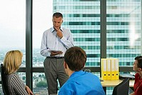 Mature businessman talking to colleagues in meeting room, reading document, hand on chin
