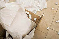 Paper and packing foam in open cardboard box, close-up