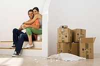 Couple moving house, taking tea break at bottom of staircase near stack of boxes, smiling, portrait