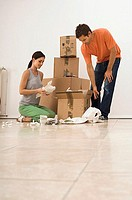 Couple moving house, packing boxes with crockery wrapped in paper, smiling, surface level