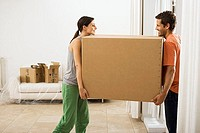 Couple moving house, carrying large cardboard box in sparse room, face to face, smiling, profile