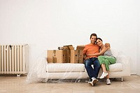 Couple moving house, sitting on white sofa wrapped in plastic sheet beside boxes, smiling, portrait