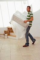 Man moving house, carrying white chair wrapped in plastic sheet in sparse room, smiling, side view