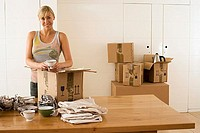 Woman moving house, packing crockery wrapped in paper in box on dining room table, smiling, portrait