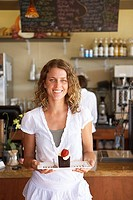 Waitress working behind counter in cafe, focus on woman carrying dessert, smiling, portrait