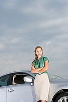 Businesswoman standing beside car, arms folded, smiling, portrait, low angle view