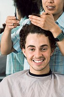 Hairdresser cutting man´s hair in barbers shop, smiling, front view, close-up, portrait