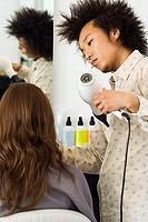 Young male hairdresser blow-drying woman's hair with hair dryer in salon, rear view