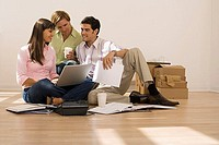 Business partners sitting on floor in office beside floor socket and documents, woman using laptop
