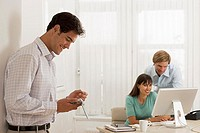 Business colleagues working at desk in office, focus on man using electronic organiser in foreground
