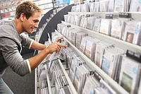 Young man sifting through CDs in record shop, bending down, smiling, side view tilt