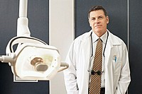 Male dentist standing beside surgical light in dental surgery, smiling, front view, portrait