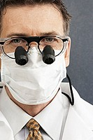 Male dentist wearing surgical mask and surgical loupes, close-up, front view, portrait (thumbnail)