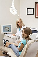 Teenage girl 14-16 sitting in chair in dental surgery, dentist in background, smiling, portrait