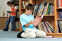 Boy 10-12 kneeling on floor beside bookshelf in library, reading book, focus on foreground