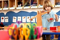 Multi-coloured scissors in classroom, focus on boy 4-6 playing with weight scale in background