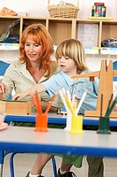 Boy 4-6 and teacher playing with weight scale on desk in classroom, smiling differential focus