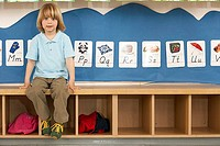 Blonde boy 4-6 sitting on bench in classroom, front view, portrait, alphabet cards on wall