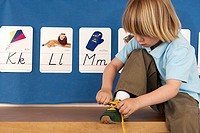Blonde boy 4-6 sitting on bench in classroom, tying shoelace, alphabet cards on wall