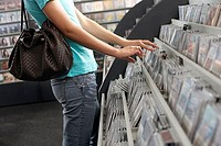 Young woman sifting through CDs in record shop, side view, mid-section
