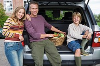 Two generation family posing beside car boot with basket of vegetables, smiling, portrait