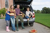 Family posing beside car boot with basket of vegetables in driveway, smiling, portrait