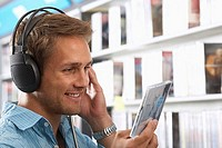 Young man wearing headphones, listening to CDs in record shop, smiling, close-up, side view