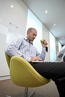 Businessman sitting in office lobby, using laptop in lap, eating apple, side view, low angle view