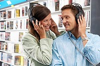 Young couple wearing headphones, listening to CDs in record shop, smiling