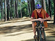 Active senior man cycling through woodland, smiling, front view, portrait