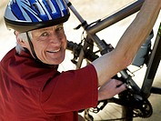 Active senior man in cycling helmet crouching beside bicycle, smiling, side view, portrait