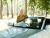 Senior woman standing beside convertible car, smiling, portrait