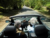 Senior couple driving in convertible car along country road, rear view, elevated view