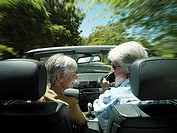 Senior couple driving in convertible car along country road, face to face, smiling, rear view