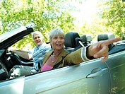 Senior couple driving in convertible car along country road, woman pointing, side view tilt