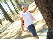 Active senior woman leaning against tree, stretching leg, side view tilt