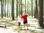 Active senior couple in sportswear taking break from jogging, woman stretching, man drinking water