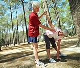 Active senior couple in sportswear exercising, woman stretching, man assisting, side view