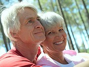 Senior couple in sportswear sitting in wood, man embracing woman, smiling, close-up, portrait