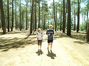 Senior couple in sportswear jogging through woodland, smiling, front view