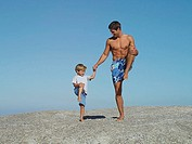 Father and son 4-6 playing on rock, standing on one leg, smiling, man in swimming shorts