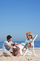 Family relaxing on beach, girl 2-4 on mother's lap in deckchair, wearing sun hats, side view