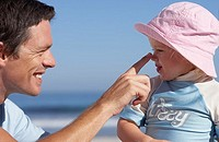Father and daughter 2-4 playing on beach, man touching girl's nose, smiling, profile
