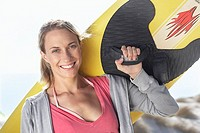 Young woman carrying yellow surfboard on shoulder on beach, smiling, close-up, portrait