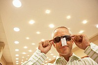 Mature man trying on pair of sunglasses in shop, price tag attached, smiling, low angle view