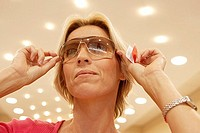 Mature blonde woman trying on pair of sunglasses in shop, smiling, close-up, low angle view