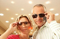 Mature couple trying on sunglasses in shop, price tag attached, smiling, portrait, low angle view