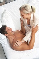 Couple playfighting in bed, woman sitting on top of man, smiling, side view, elevated view